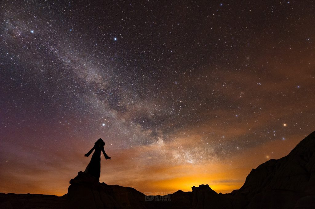 Creepy robed silhouette standing on badlands formation under Milky Way.