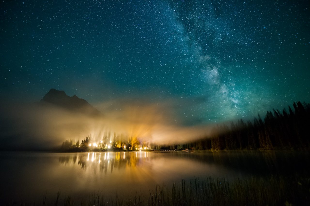 Lights from Emerald Lake Lodge pierce through low mist while Milky Way sets in the night sky.