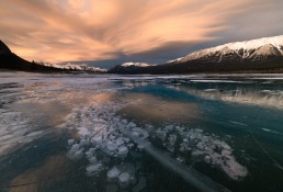 Lenticular clouds colored orange by Sunset over frozen methane bubbles at Abraham Lake