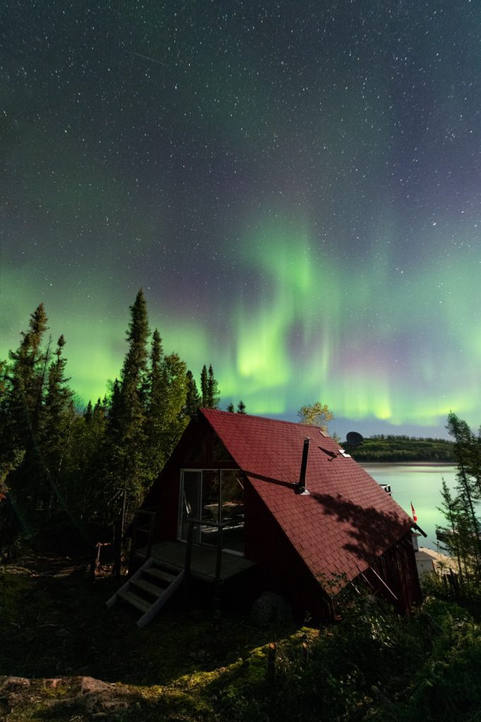 Red roofed cabin in Northern Alberta with Aurora Borealis dancing in the sky