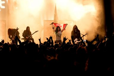 Alissa White-Gluz holds a Canadian flag and while Arch Enemy plays in Calgary