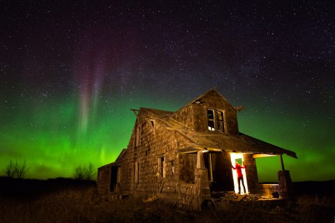 Northern lights over light painted abandoned house with illuminated woman in doorway