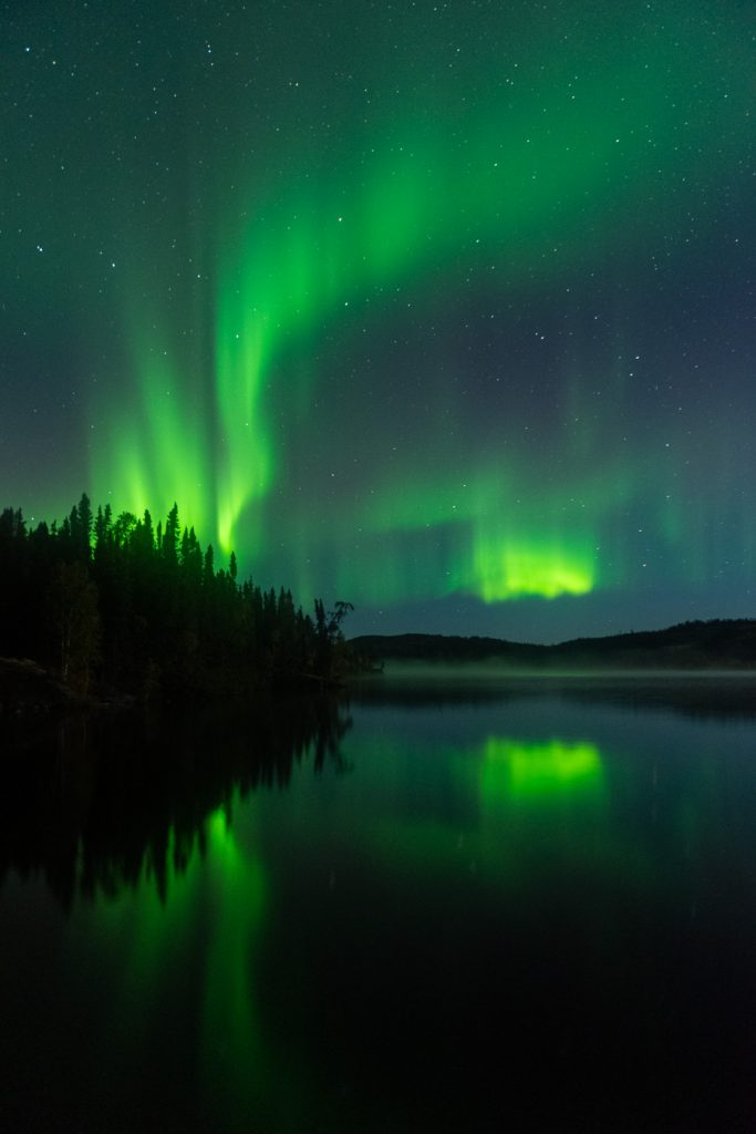 Aurora borealis reflecting in Andrew Lake, Northern Alberta