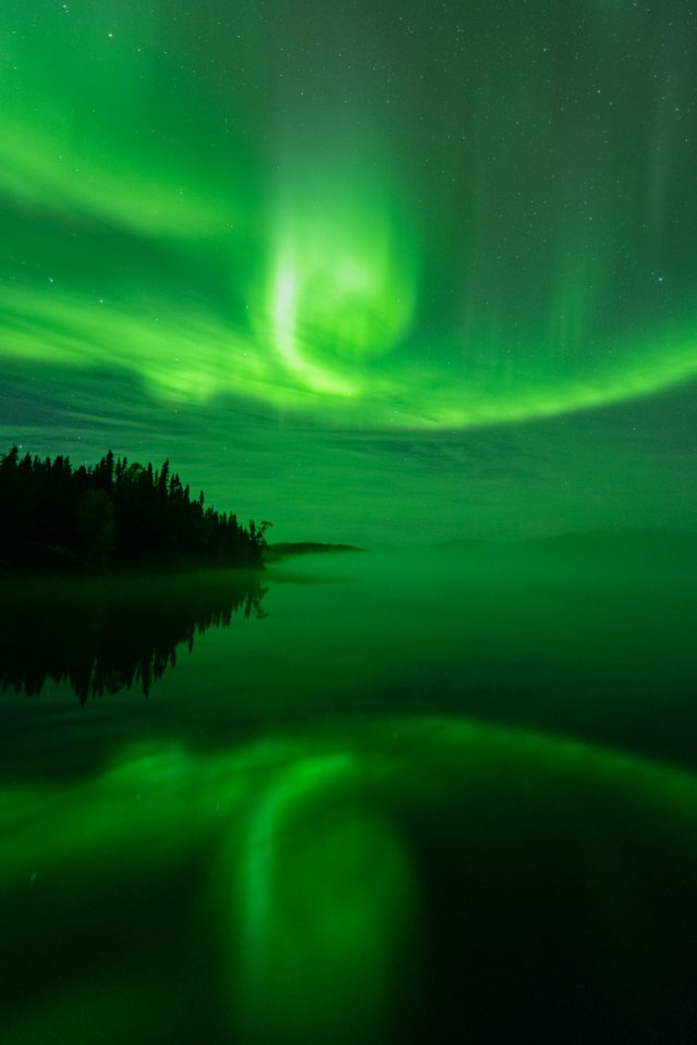 Green aurora borealis making a swirl shape reflecting in Andrew Lake, Northern Alberta
