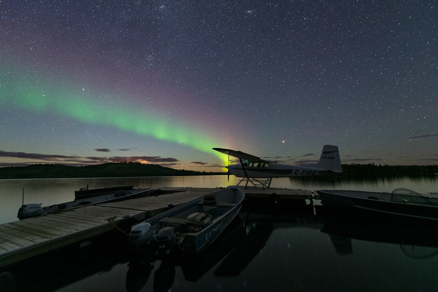 Float plane and fishing boats docked while an aurora arc forms in starry sky