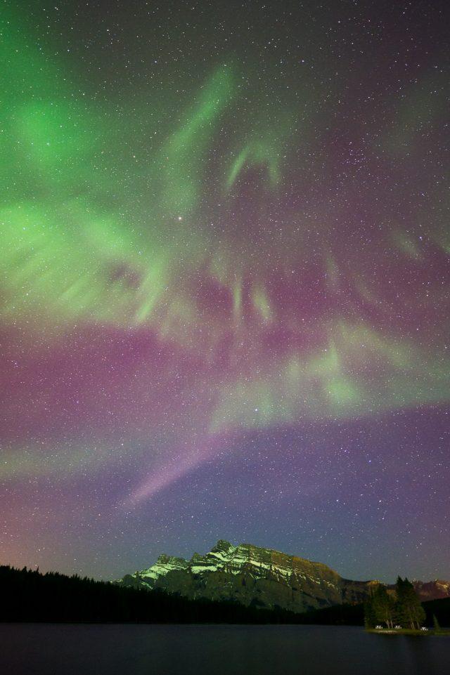 Bird shaped aurora borealis corona over Mount Rundle at Two Jack Lake