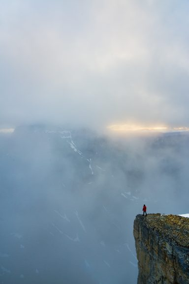 Hiker in red jacket on cliff looks at Mount Temple being revealed through clouds