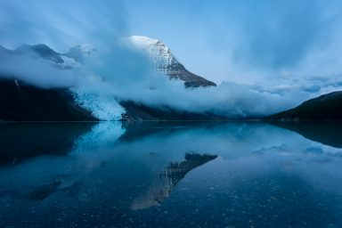 Mount Robson and low clouds reflecting in Berg Lake during blue hour