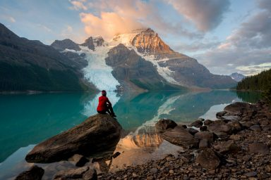 A woman in a red shirt and toque sit on a rock and watches alpen glow on Mount Robson