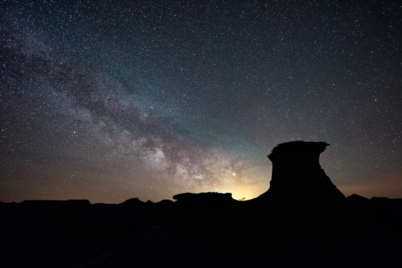 Milky Way image stacked to reduce noise with silhouette of two hoodoos - Monika Deviat