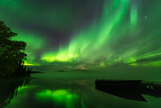Green northern lights dancing over misty Andrew Lake and fishing boat tied up to a dock