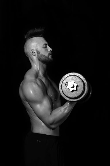 Male body builder with mohawk doing bicep curl