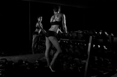 Female body builder looking at reflection at dumb bell weight rack
