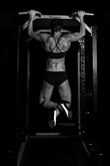 Female Body builder holding pull up position