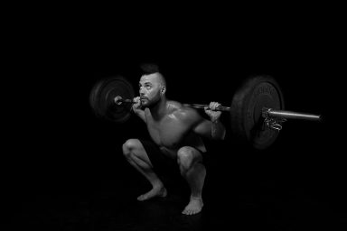 Male body builder squatting with bar