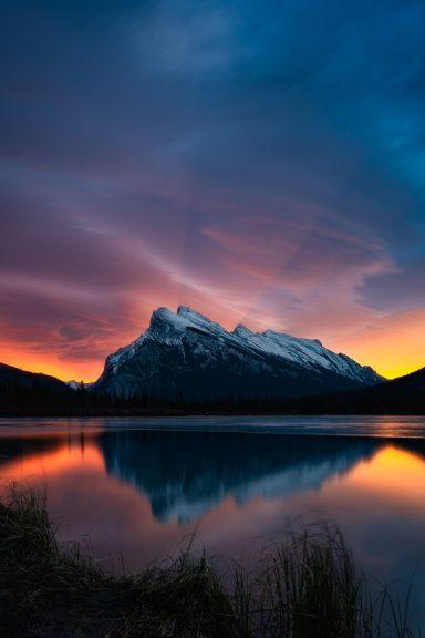 Sunrays behind Mount Rundle during dramatic sunrise at Vermillion Lakes