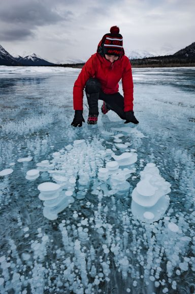 Woman in red jacket wearing micro spikes crouches to look at methane bubble formations on Abraham Lake