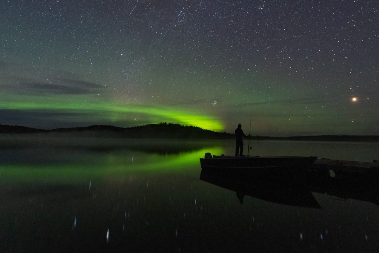 Fisherman holding fishing rod and looking out at Aurora Borealis at Northern Alberta Lake