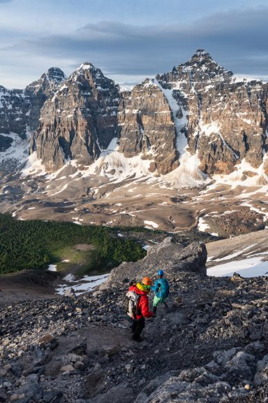 A man and woman scramble down a rocky slope in front of Deltaform Mountain and Larch Valley