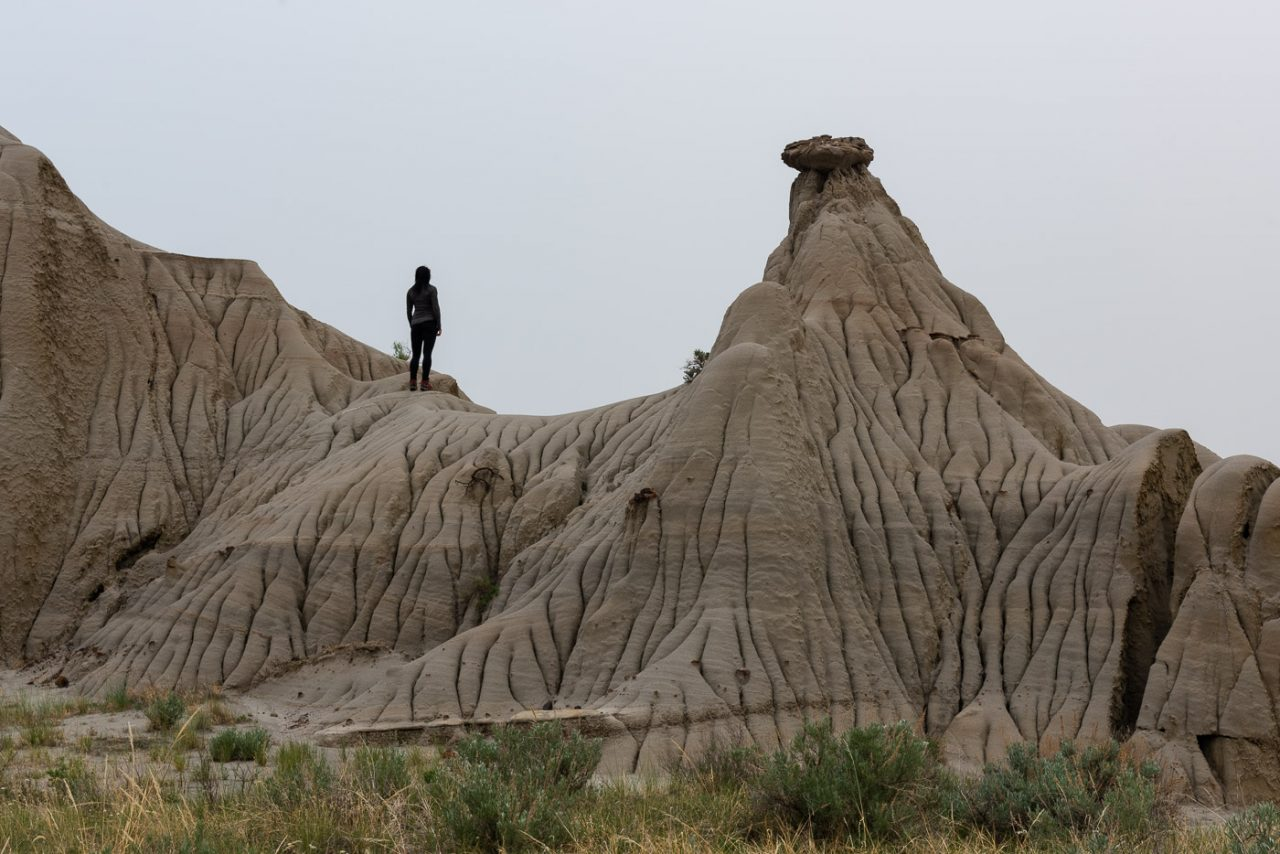 Women in black standing on formations in the badlands