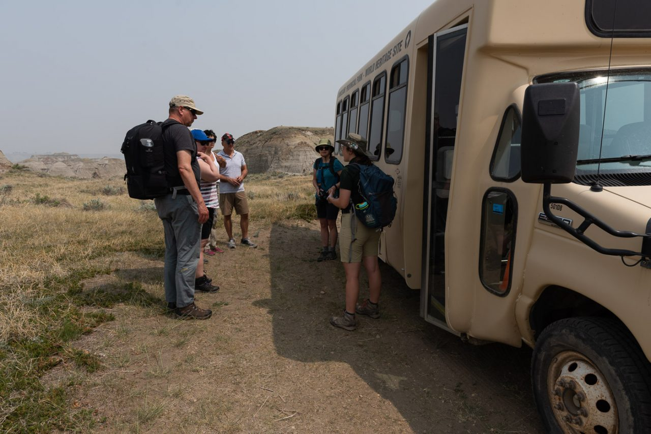 Workshop participants listening to a park guide while standing in front of a dinosaur provincial park tour bus