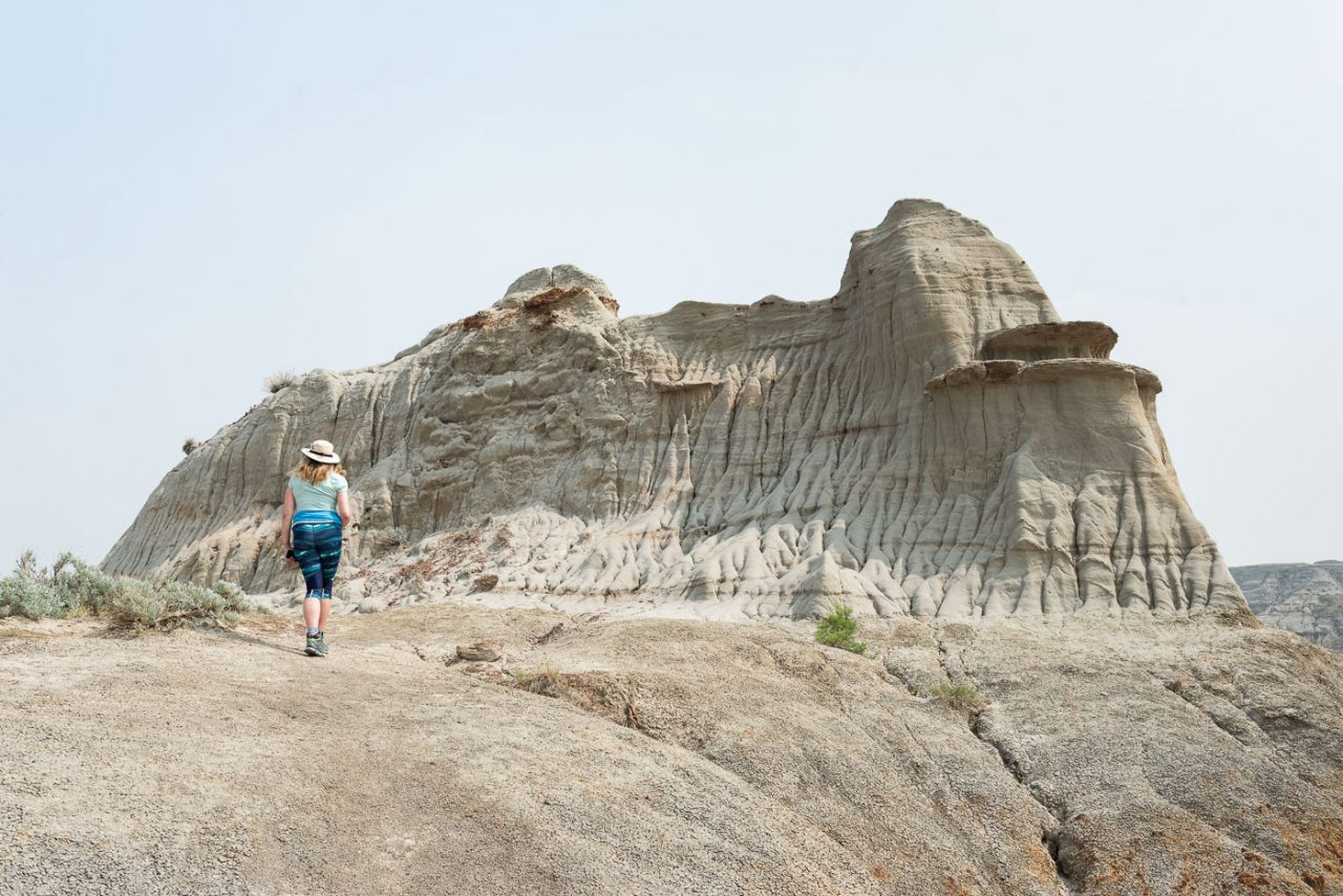 Women in blue shirt and blue patterned leggings walking towards badlands formation