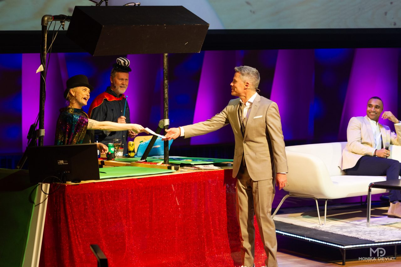 Mandy Stobo handing Dave Kelly the sponsor list which she made disappear during magic show