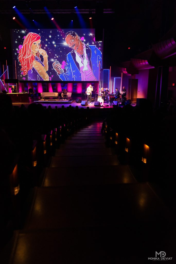 Bella Concert Hall aisle leading to stage with Dave Kelly Live on stage