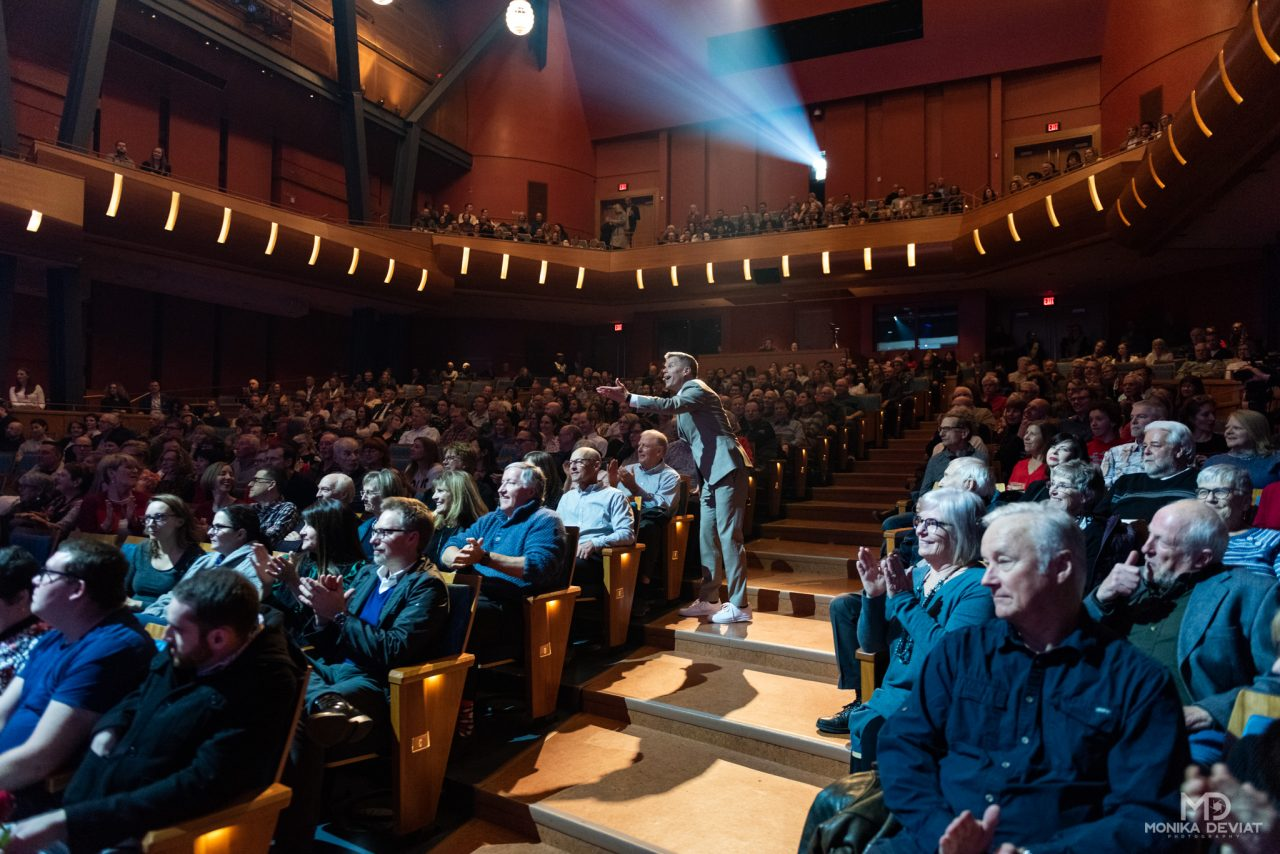 Dave Kelly walking down concert hall aisle and interacting with guests