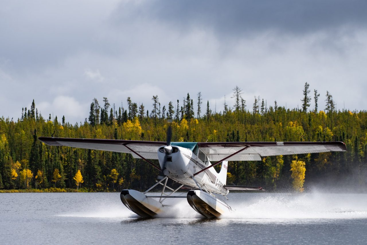 Float Plane taking off in front of fall colours at Andrew Lake in Northern Alberta