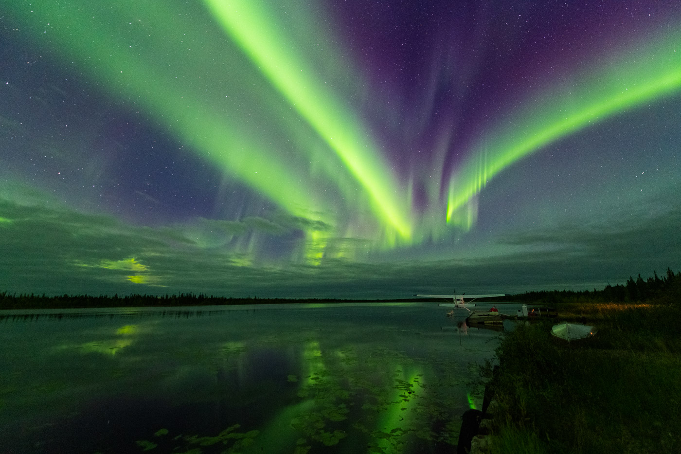 Northern lights streaking green and purple over a float plane dock in Northern Alberta