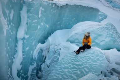 Woman in yellow jacket sitting on a glacier looking at blue ice