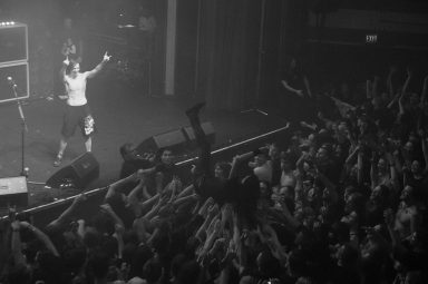 Joe Duplantier jumps into the crowd as Mario Duplantier stands on stage throwing horns, Gojira, Vancouver