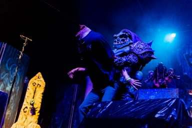 Alien character holds a decapitated human on stage, Gwar Calgary