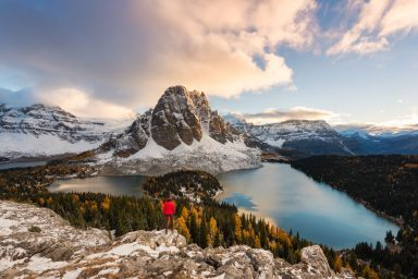 Hiker in red jacket stands on Nub Peak looking over Sunburst Lake and Larches