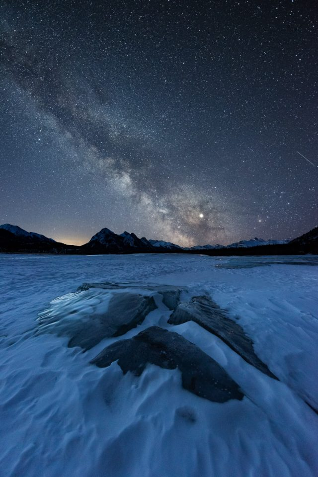 Ice cracks with methane bubbles protruding through snow with Milky Way and Ex Coulis behind