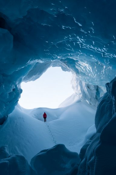 Woman in red jacket walking up a snow slope out of a massive ice cave in the Canadian Rockies
