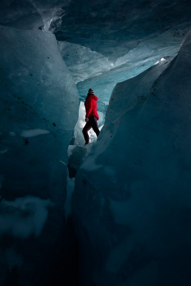 Woman in red jacket walking between massive ice blocks in an Ice Cave Jasper National Park