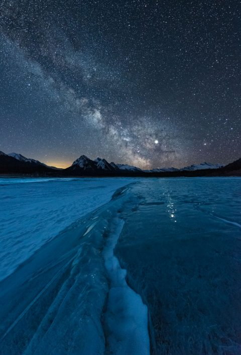 Ice cracked on frozen lake with Milky Way and Jupiter, Nordegg