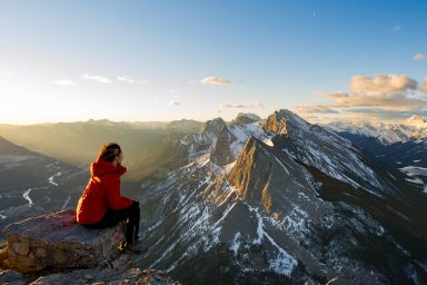 Female hiker in red jacket sits on rock and looks at alpen glow hitting Ha Ling peak