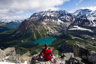 Female hiker in red shirt sits on the edge of cliff and looks down at Lake O'hara