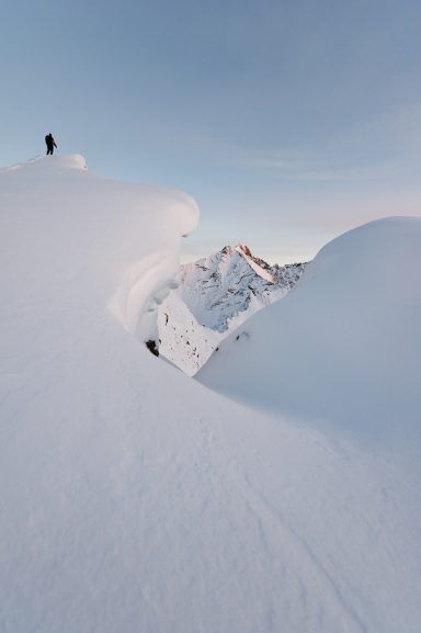 Hiker stands on snowy and corniced ridge in Highwood Pass