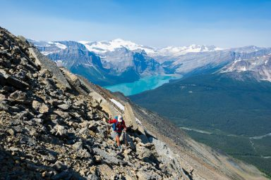 Hiker navigates a rocky slope with Lake Hector reflecting peaks in the background