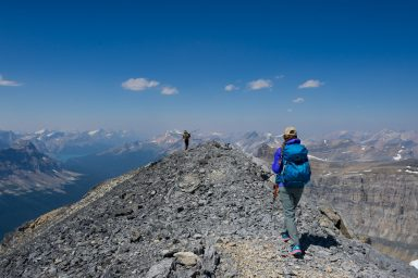 Two hikers walk along the summit ridge of Little Hector, forest fire smoke in the air