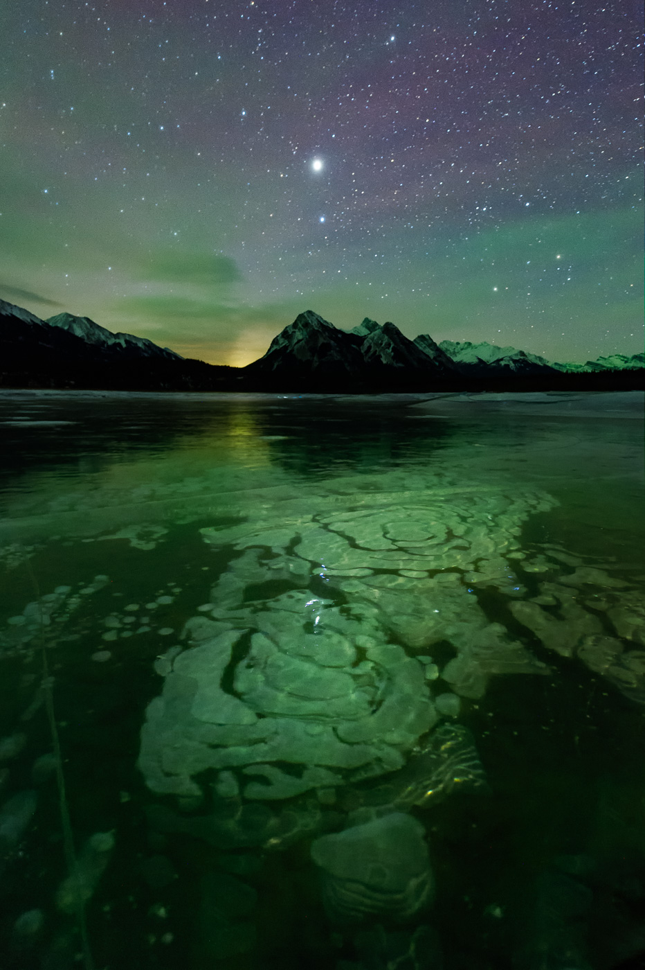 Methane bubbles trapped in ice lit up by Northern Lights at Abraham Lake with Venu above Ex Coulis