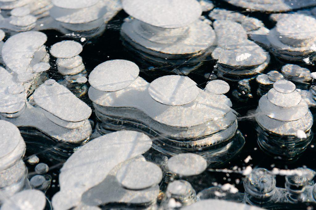 Tiny Methane Bubbles refracting rainbows in frozen Lake Minnewanka