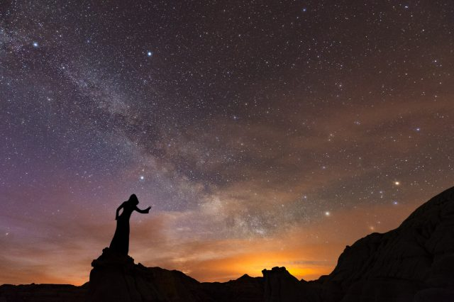 Cloaked silhouette standing on sandstone ridge with Milky Way at Dinosaur Provincial Park