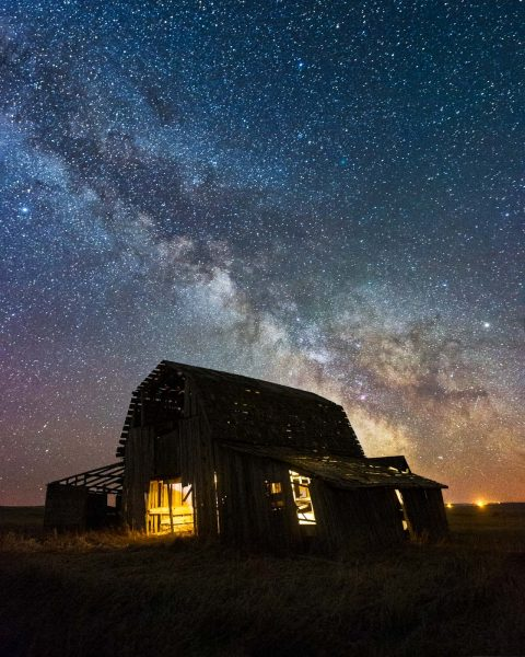 Milky Way looming over dilapidated barn in Alberta