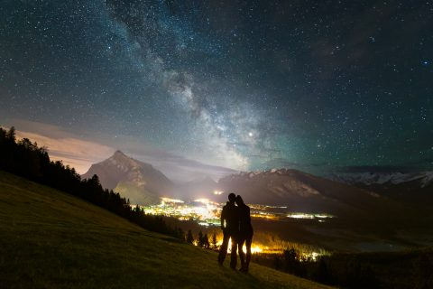 Silhouette of couple above the town of Banff with Milky Way