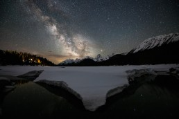 Milky Way over Mount Engadine Meadows reflecting in a still creek with snowy banks